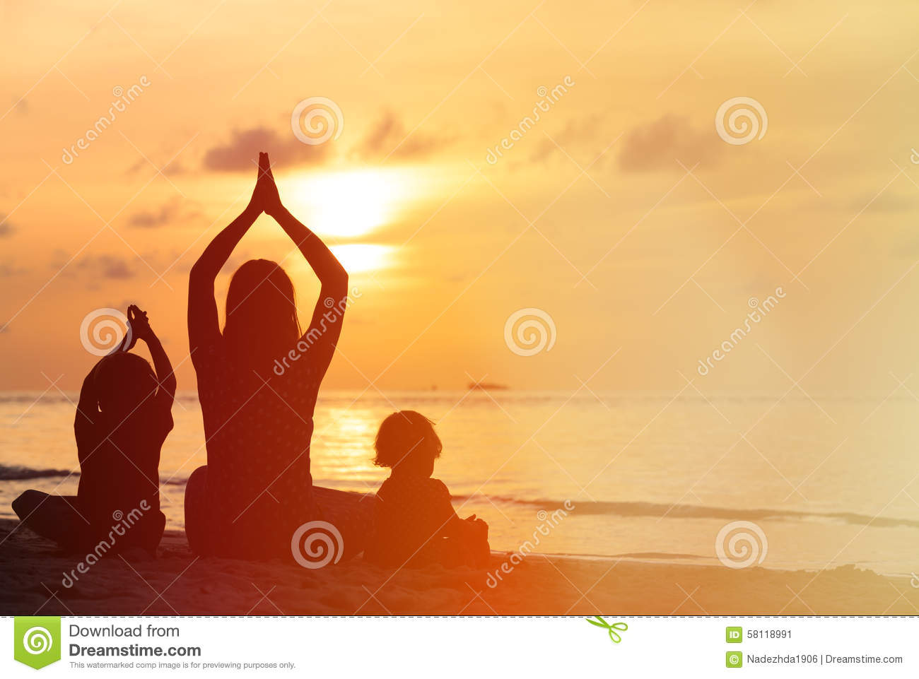 Silhouette of mother and kids doing yoga at sunset