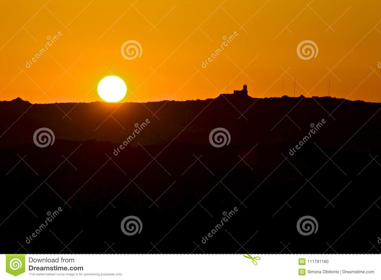 Silhouette of mountain and the sun at sunset with orange sky