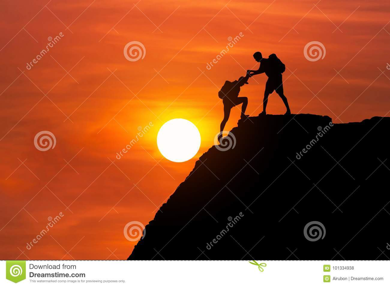 Silhouette mountaineer gives helping hand his friend to climb high cliff mountain together.