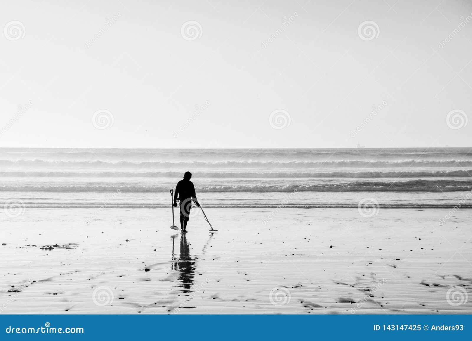 Silhouette noire et blanche d un mâle employant un détecteur de métaux recherchant le trésor à marée basse