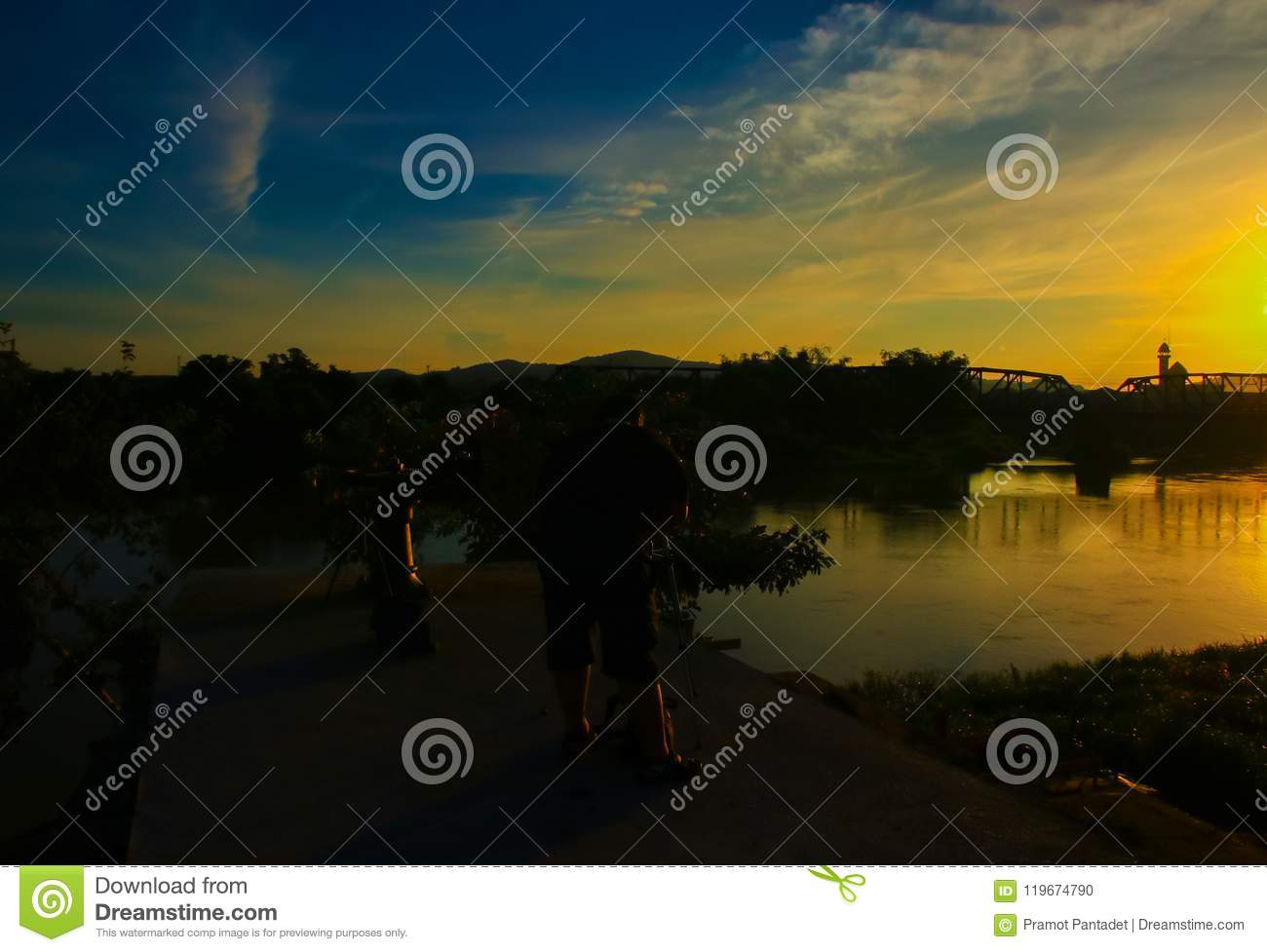 Silhouette of obese male photographer taking picture in sunrise the morning with copy space add text