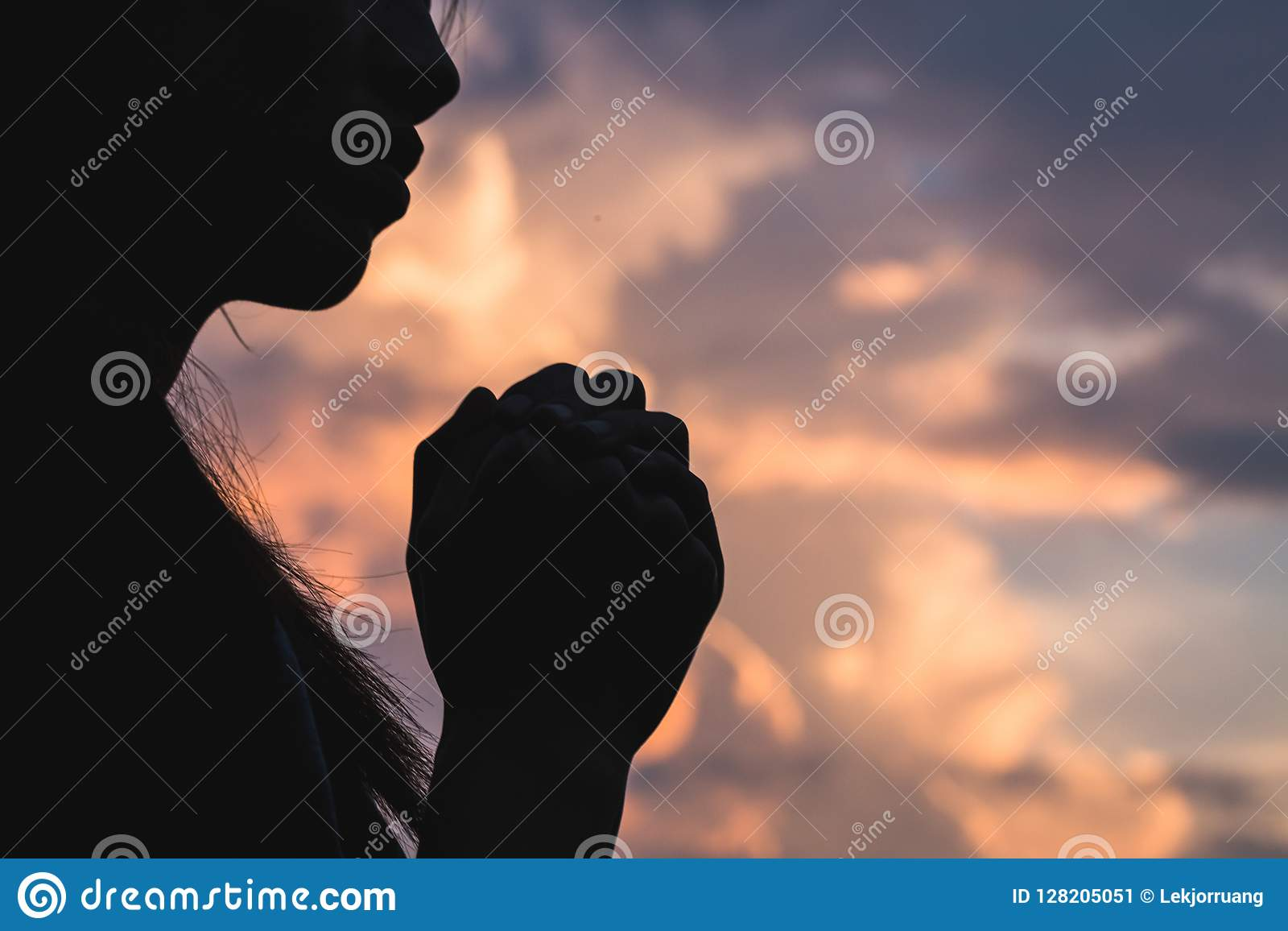 Silhouette off young woman praying for God`s blessings with th