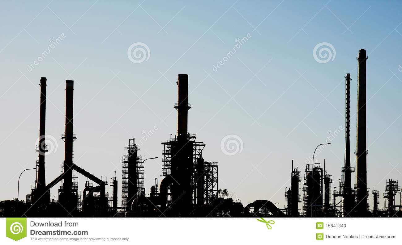Silhouette Of An Oil Refinery With Chimneys Stock Photos