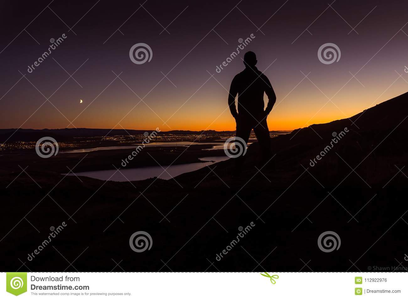 Silhouette Overlooking a city at sunset