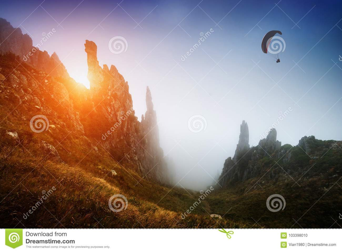Download Silhouette Of Paraglider Over The Misty Mountain Valley Stock Photo - Image of alps, athlete: 103398010