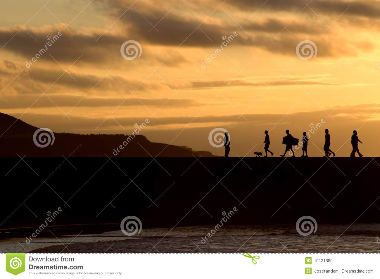 Silhouette of people walking at sunset