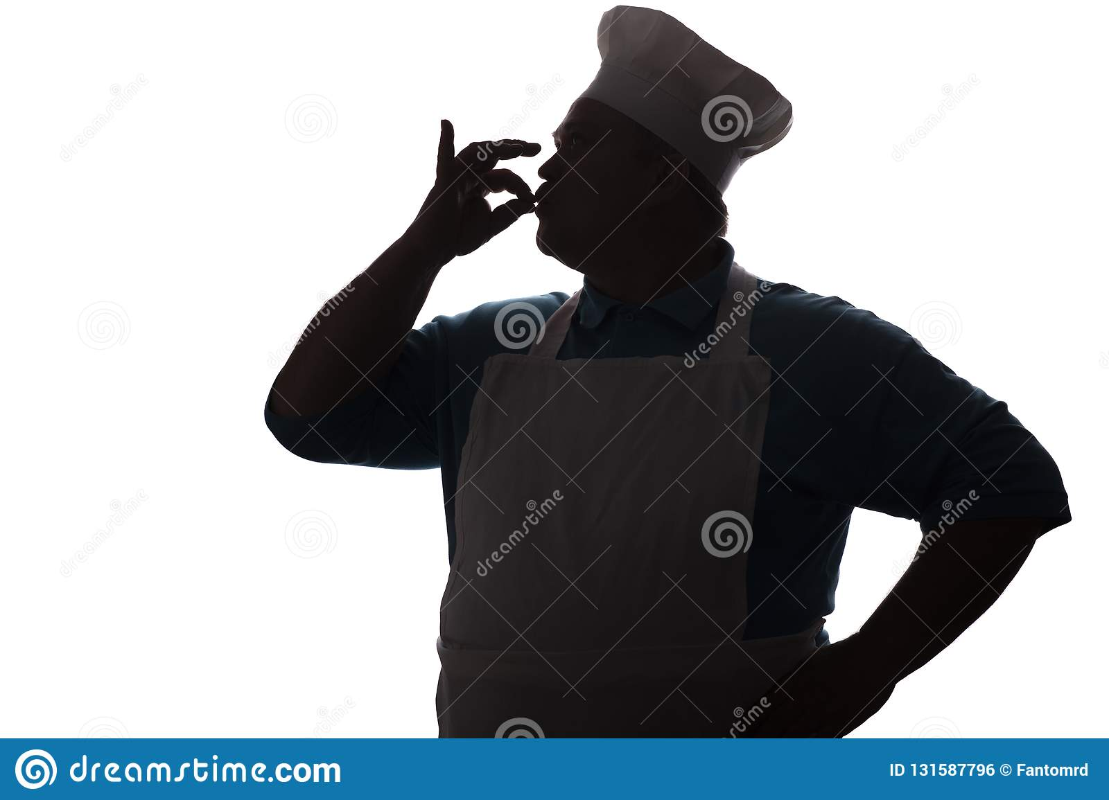 Silhouette of a happy chef kissing fingers out of delicious dishes, a person`s profile in a kitchen uniform showing ok by h