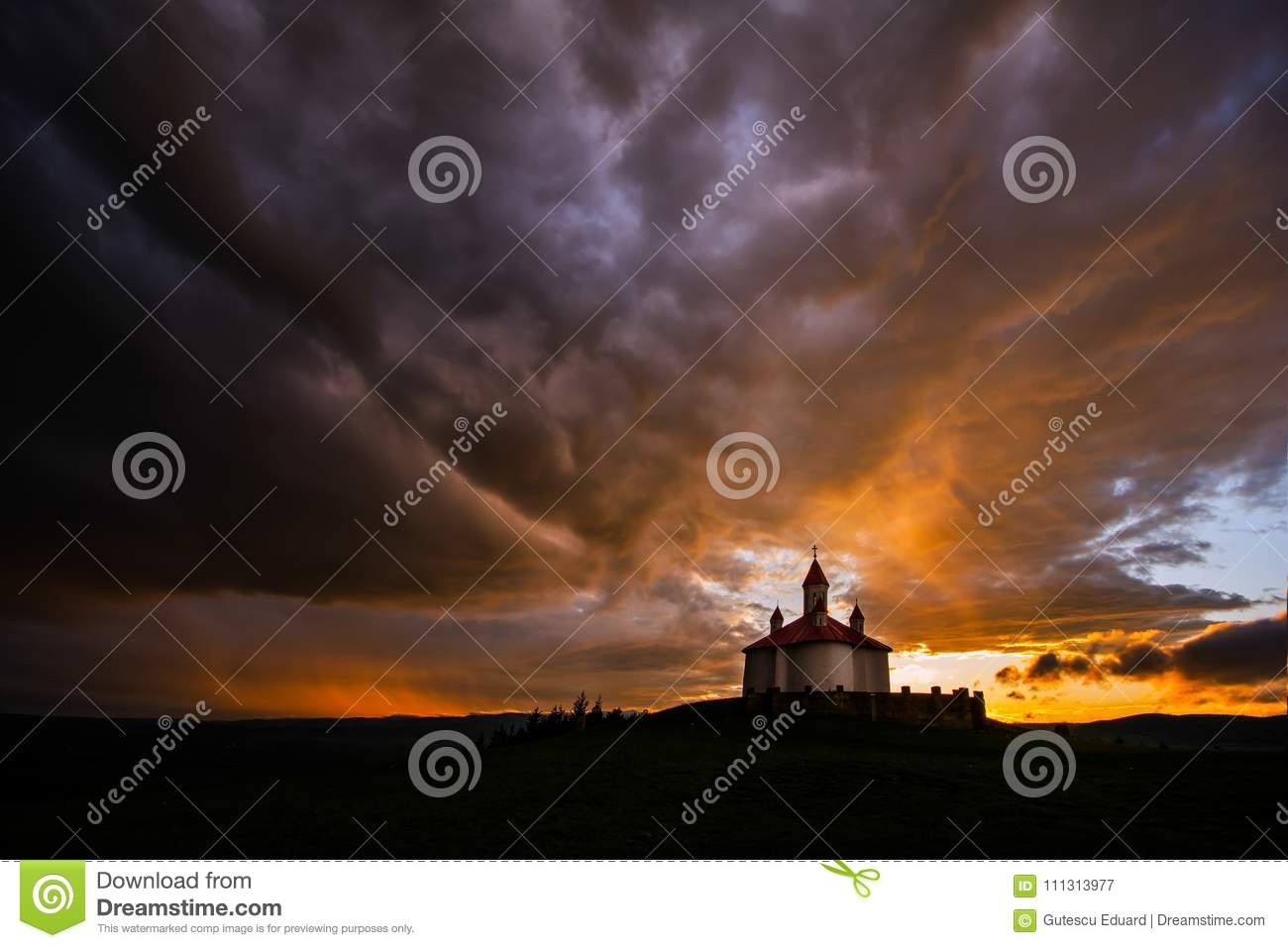 Silhouette of Romanian church with ray light after storm
