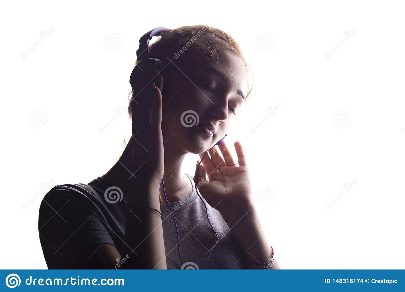 Silhouette of a romantic girl listening to music in headphones, young woman relaxing on a white isolated background, concept of