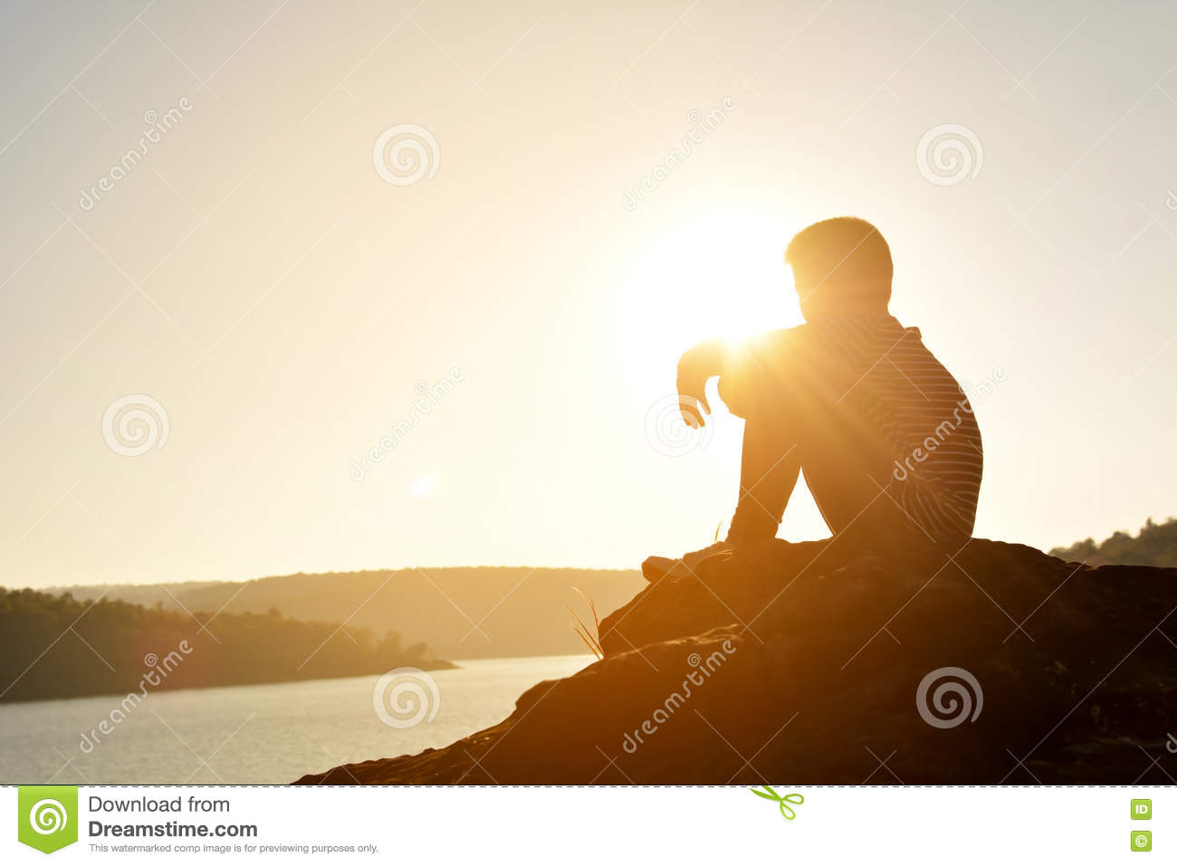 Silhouette of sad boy and sitting on the rock in river at the sky sunset