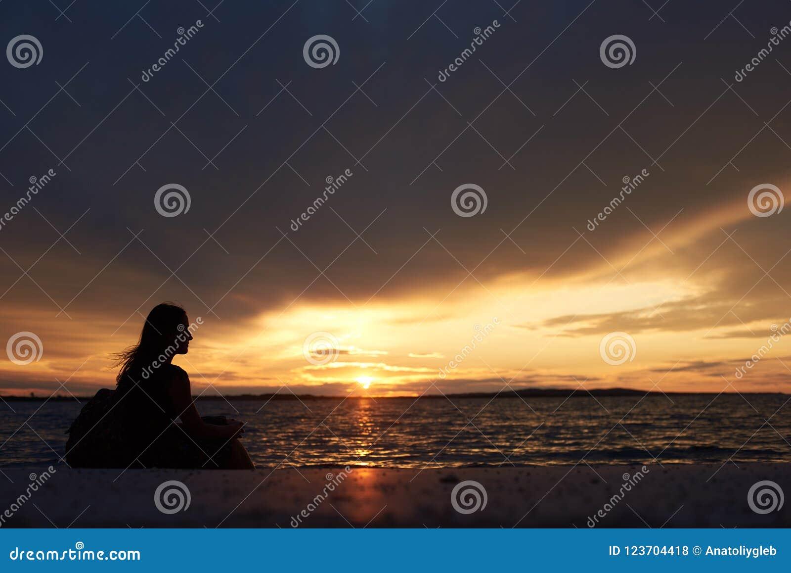 Silhouette seule de femme au bord de l eau, appréciant le beau paysage marin au coucher du soleil