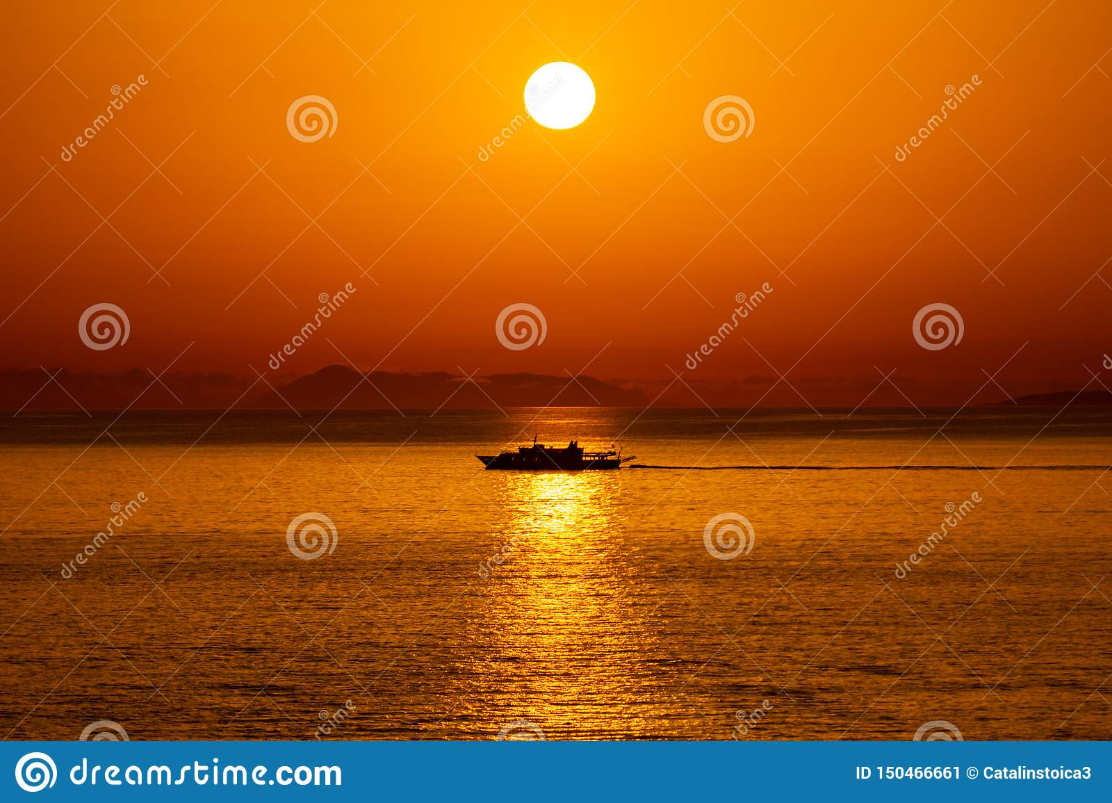 Silhouette of a ship passing in the reflection of the Sun in the Ionian Sea, Sarande, Albania.