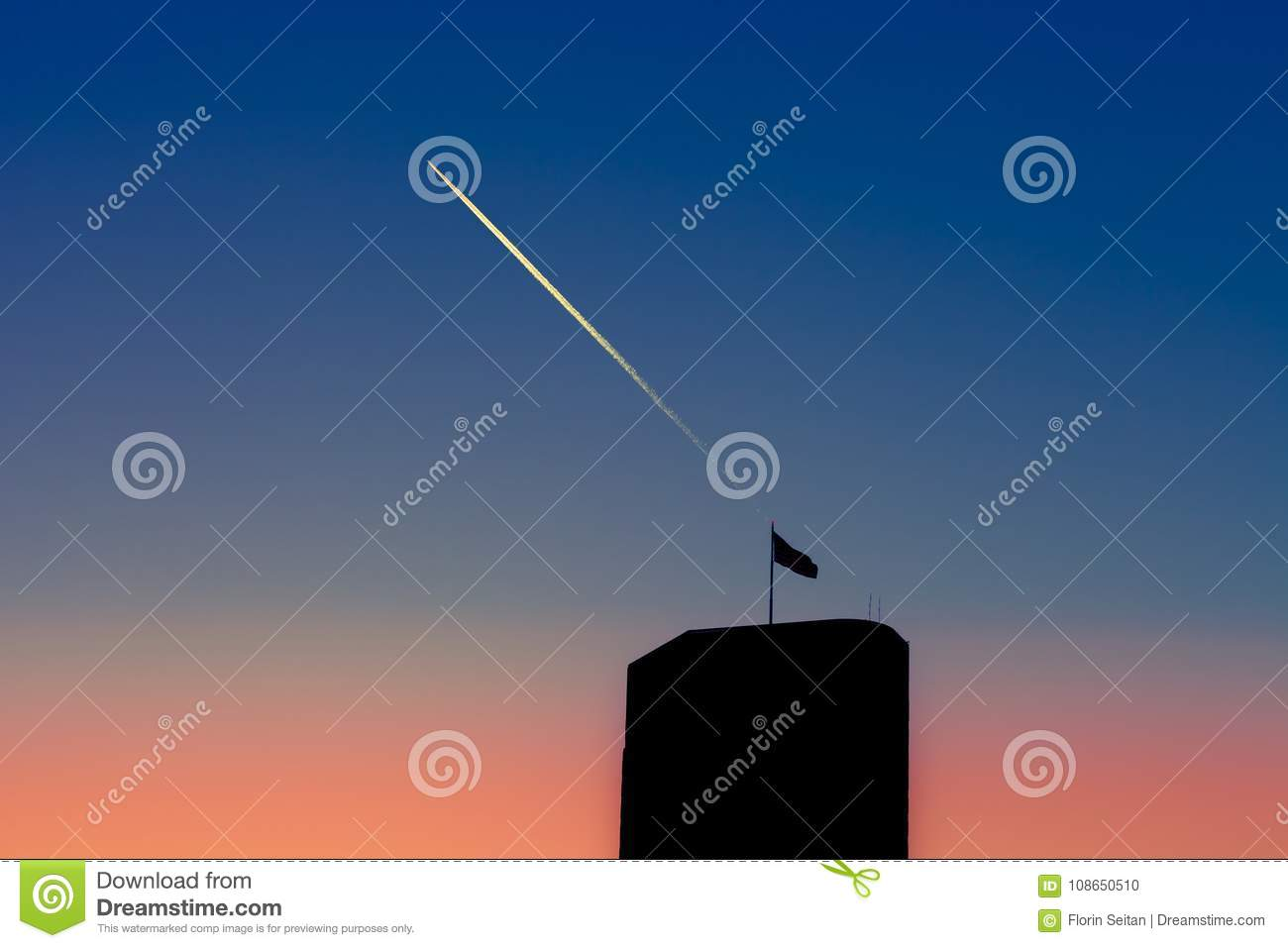 Silhouette of skyscraper with flag on top against a gradient sky with turbojet trails above