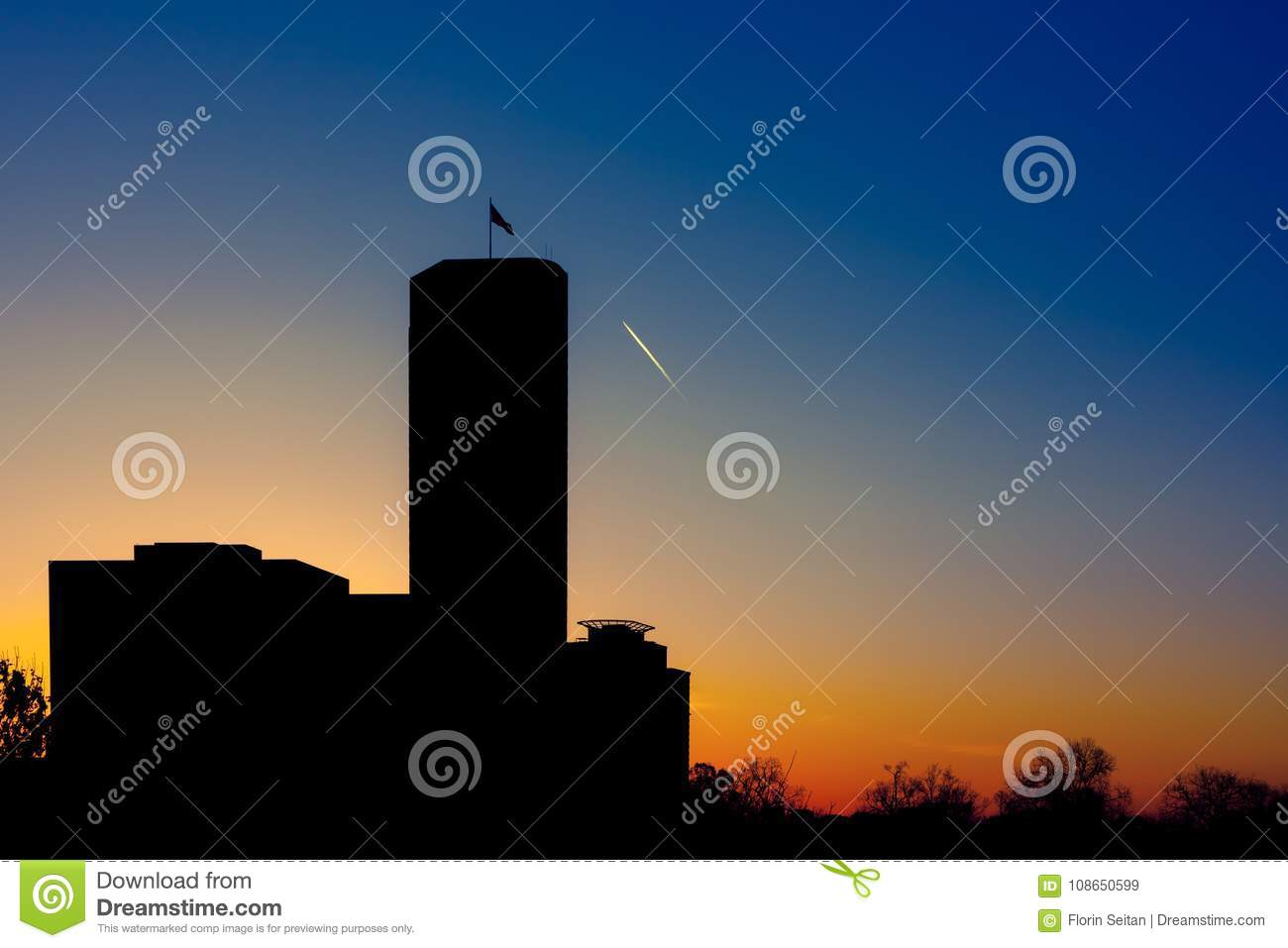 Silhouette of skyscraper with flag on top against a gradient twilight sky with turbojet trails
