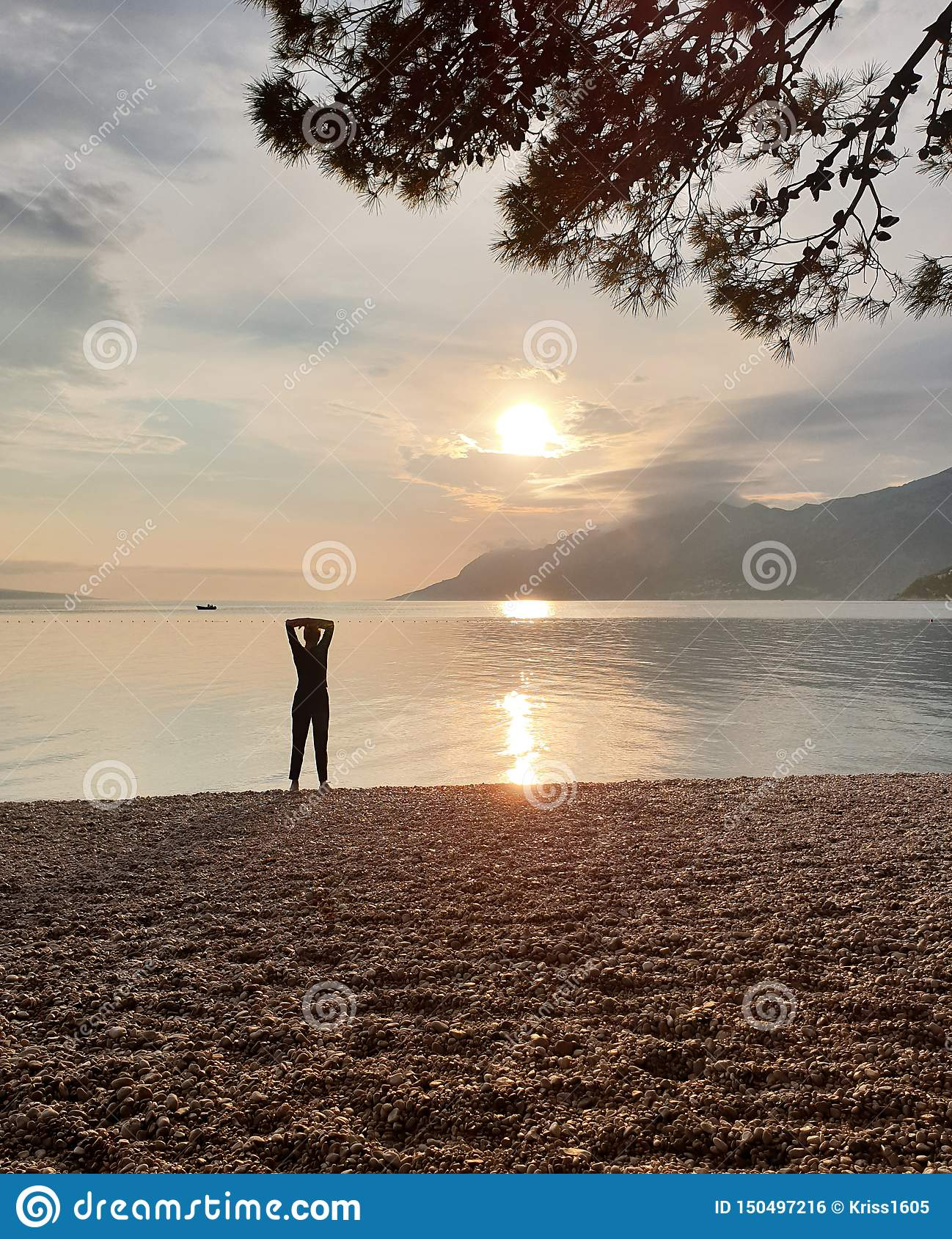 Silhouette of a slender woman looking at the sunset, which stands on the seashore.  Enjoying a relaxing summer vacation