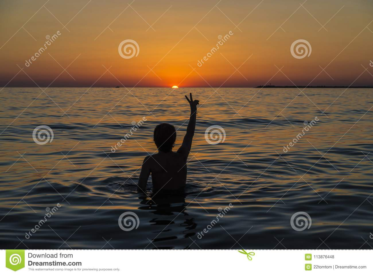 Teenager boy bathing in the sea at sunset in Sicily