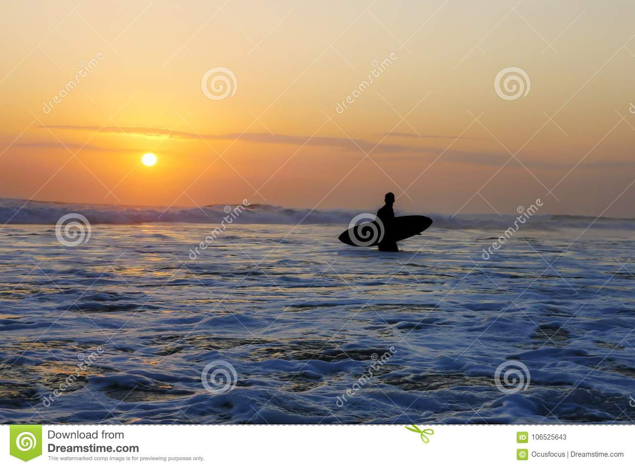 Silhouette of unknown anonymous surfer holding surf board after surfing on sunset with amazing beautiful sunlight with orange sky