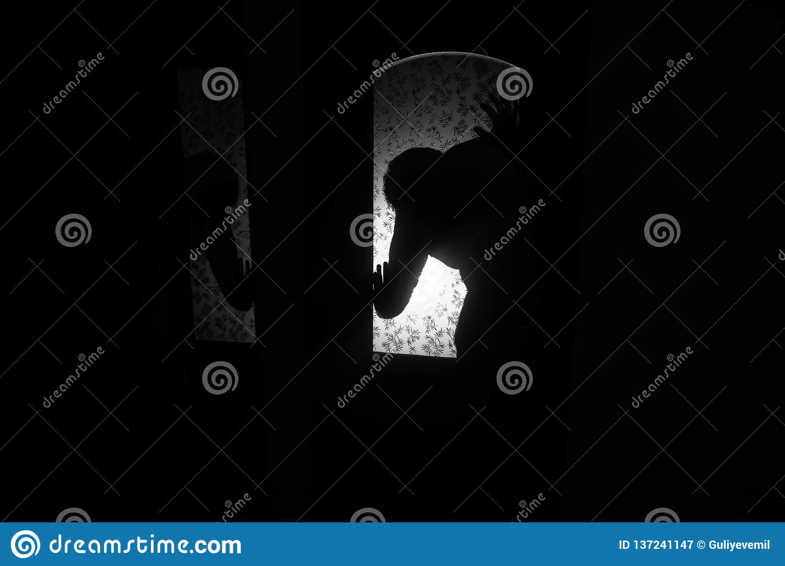 Silhouette of an unknown shadow figure on a door through a closed glass door. The silhouette of a human in front of a window at