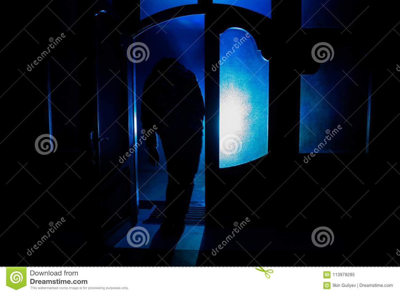 Silhouette Of An Unknown Shadow Figure On A Door Through A Closed