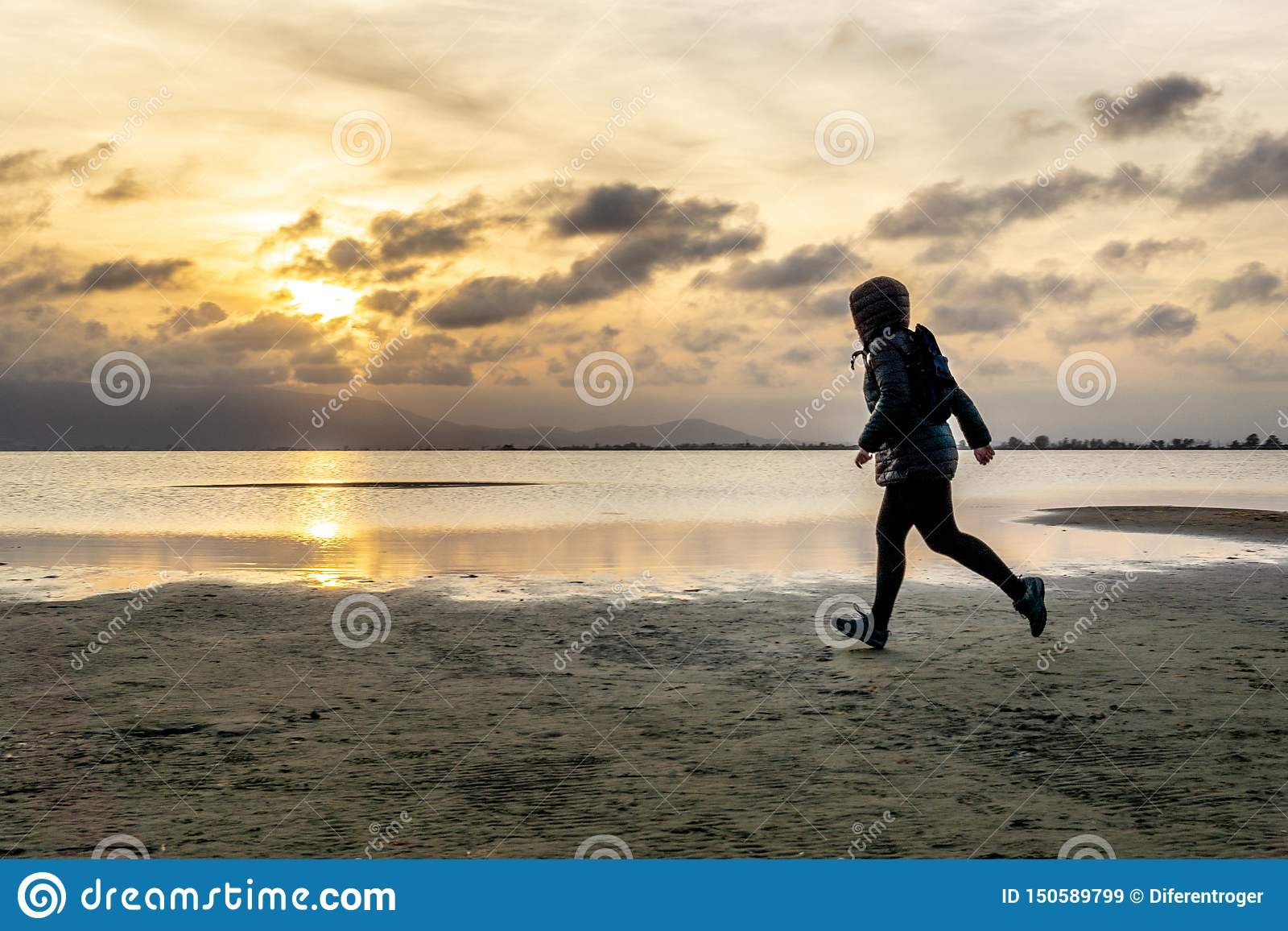 Silhouette of a unrecognizable woman walking on the beach at sunset