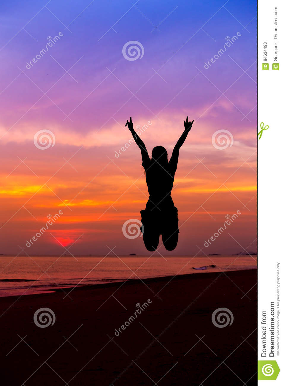 Silhouette of woman jumping with hands up and showing I LOVE YOU sign on the sea beach