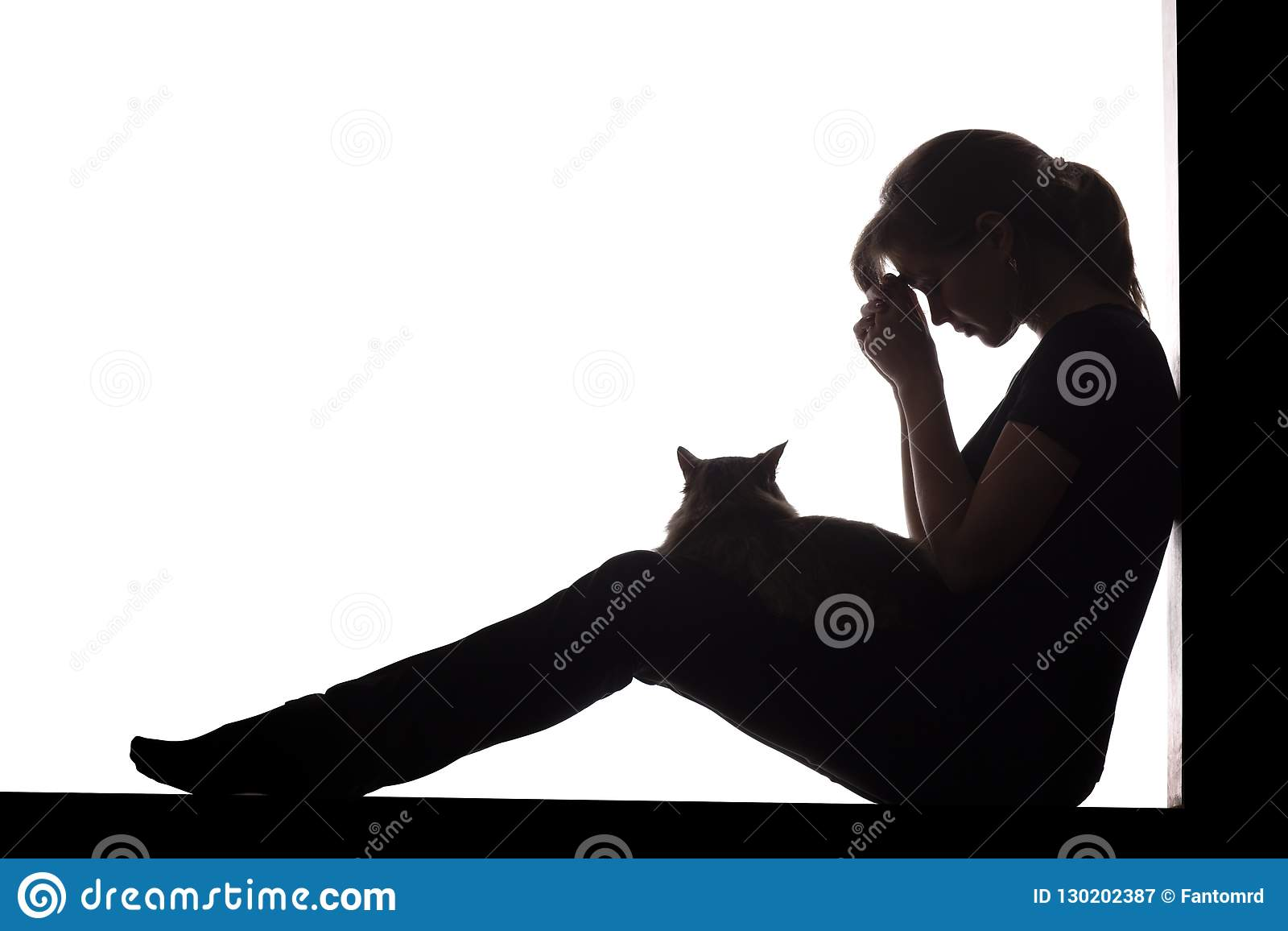 Silhouette of a woman sitting on the floor on a white isolated background with a cat in her arms, a sad girl praying