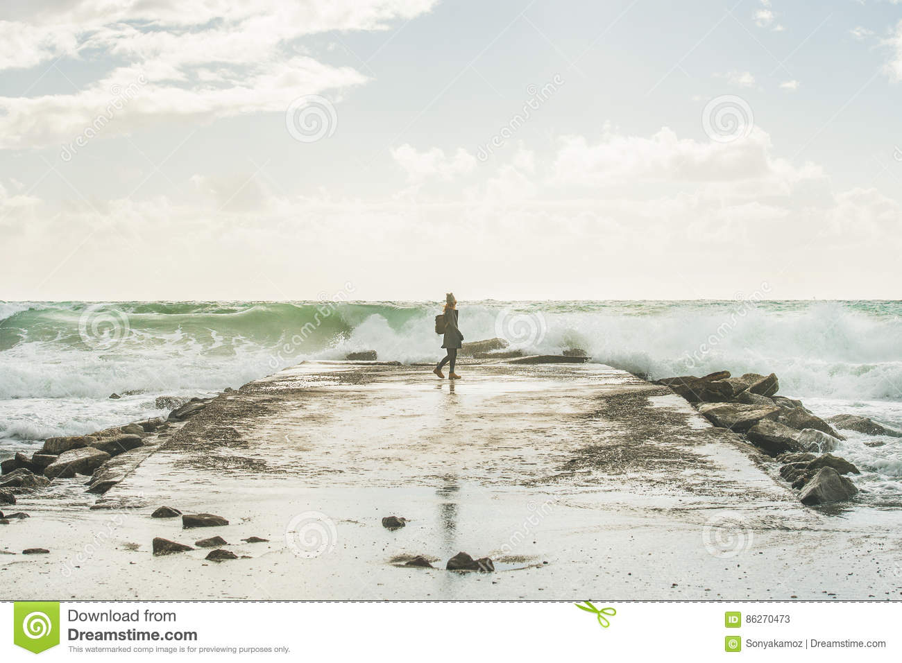 a034efb52a55 Silhouette of young woman walking on pier surrounded by stones and looking  at waves of stormy Mediterranean sea in winter