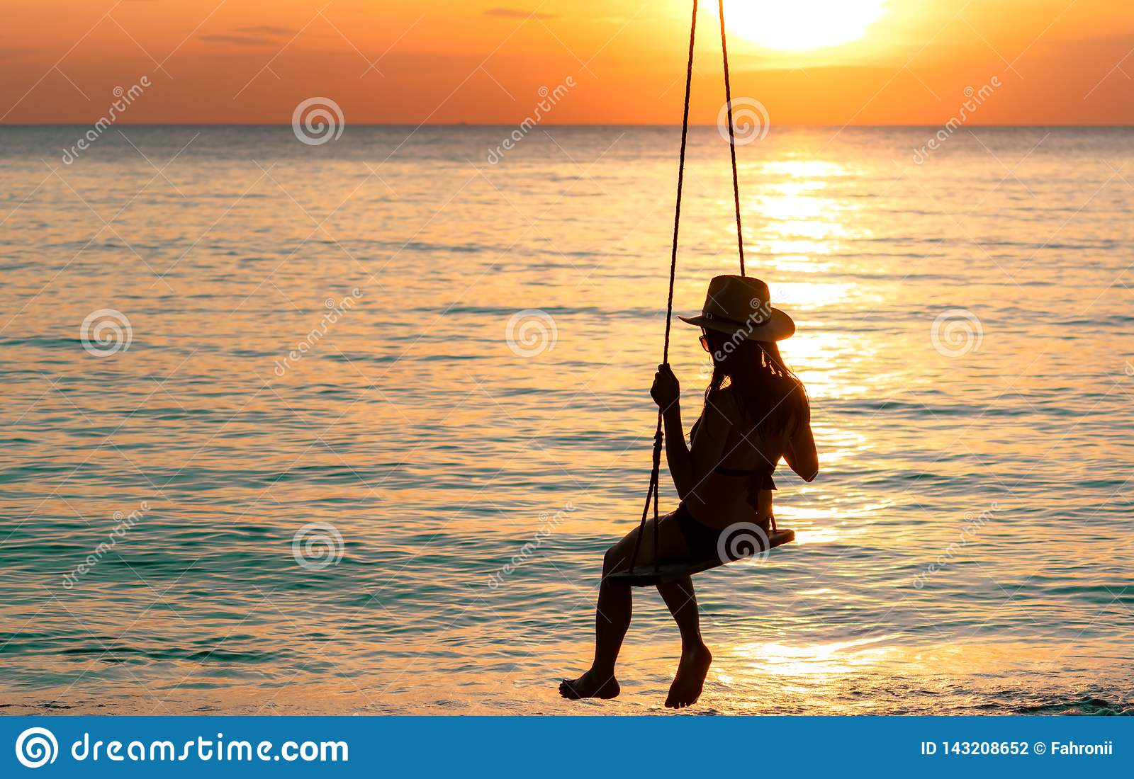 Silhouette woman wear bikini and straw hat swing the swings at the beach on summer vacation at sunset. Enjoying and relaxing girl