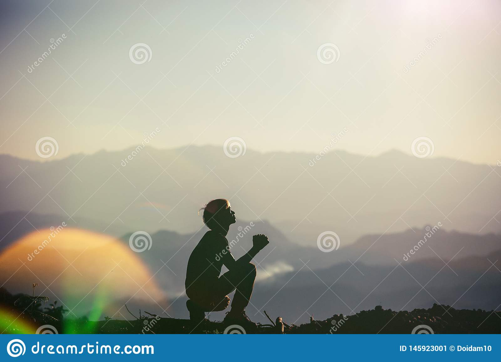 Silhouette Young asian christian man praying on sunset