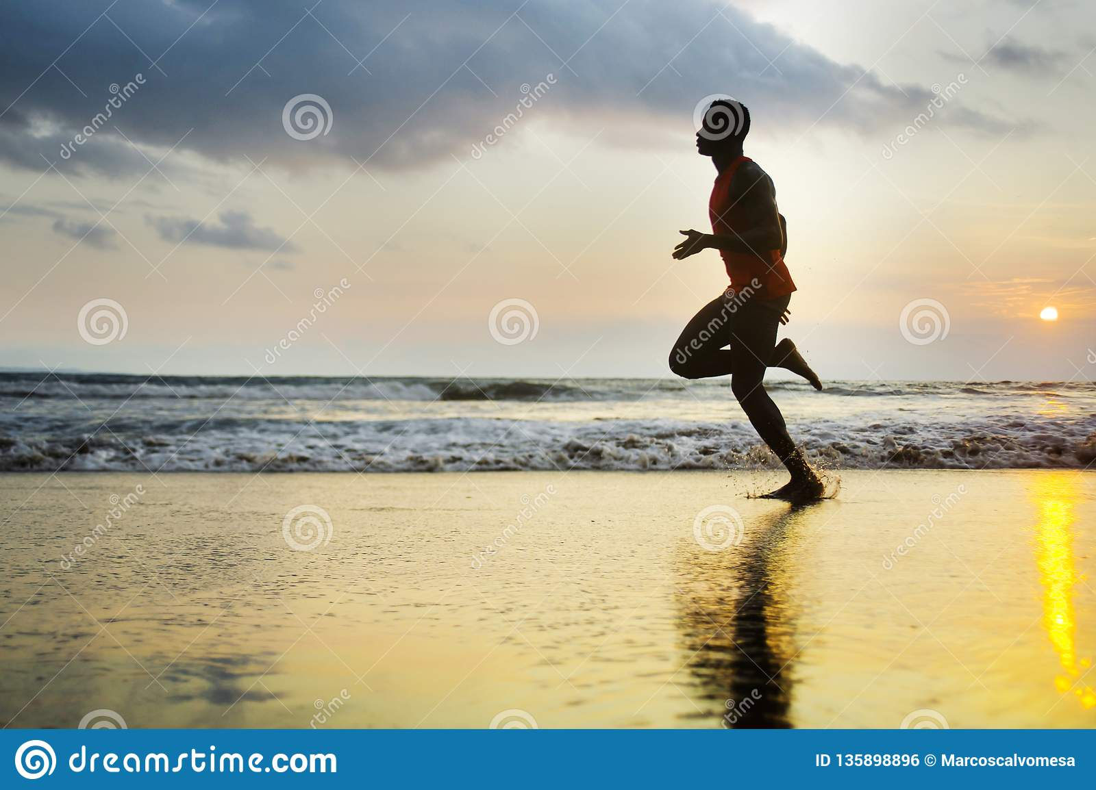 Silhouette of young attractive fit athletic and strong black afro American man running at sunset beach training hard and sprinting