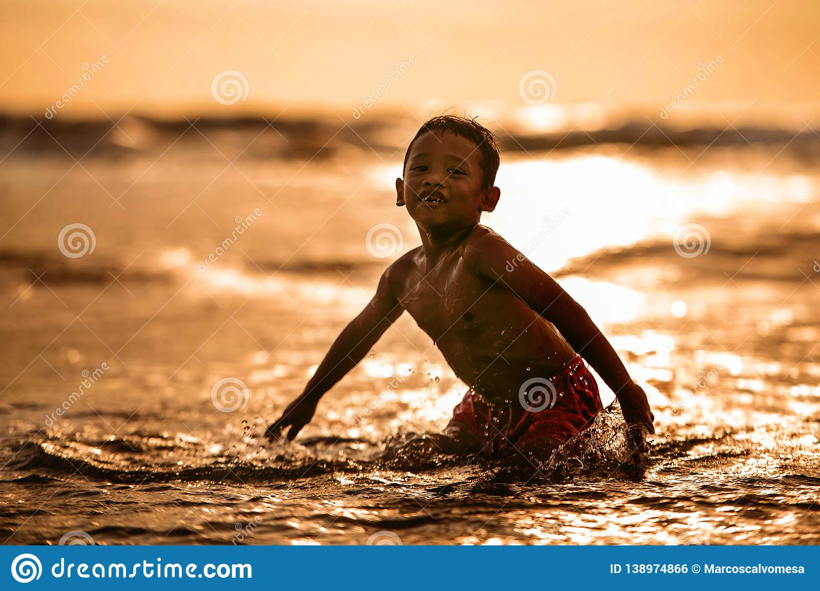 Silhouette of young boy playing crazy happy and free at the beach splashing with water playing with sea waves jumping and having