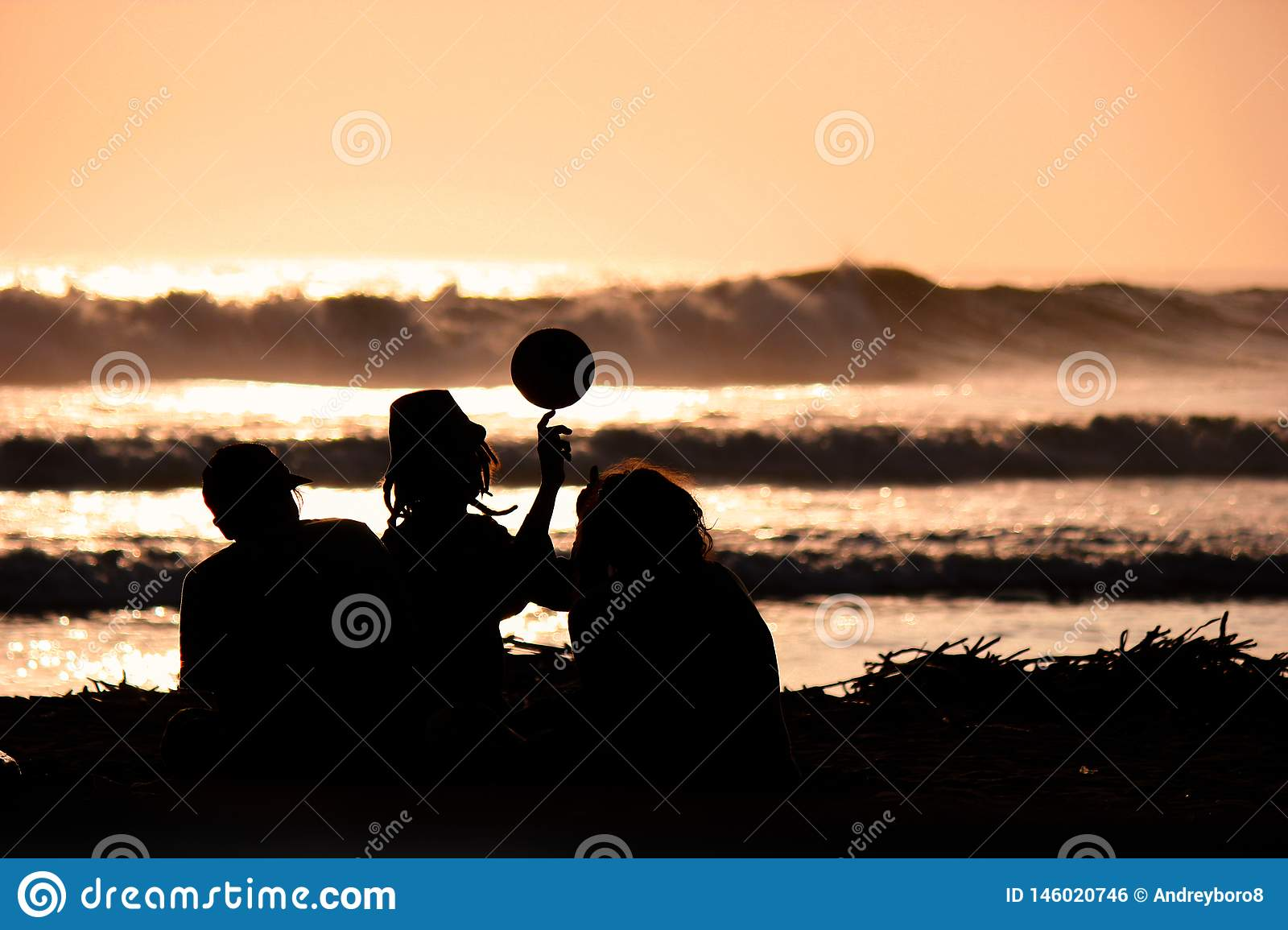 Silhouette of young friends playing with a ball on the beach on sunset