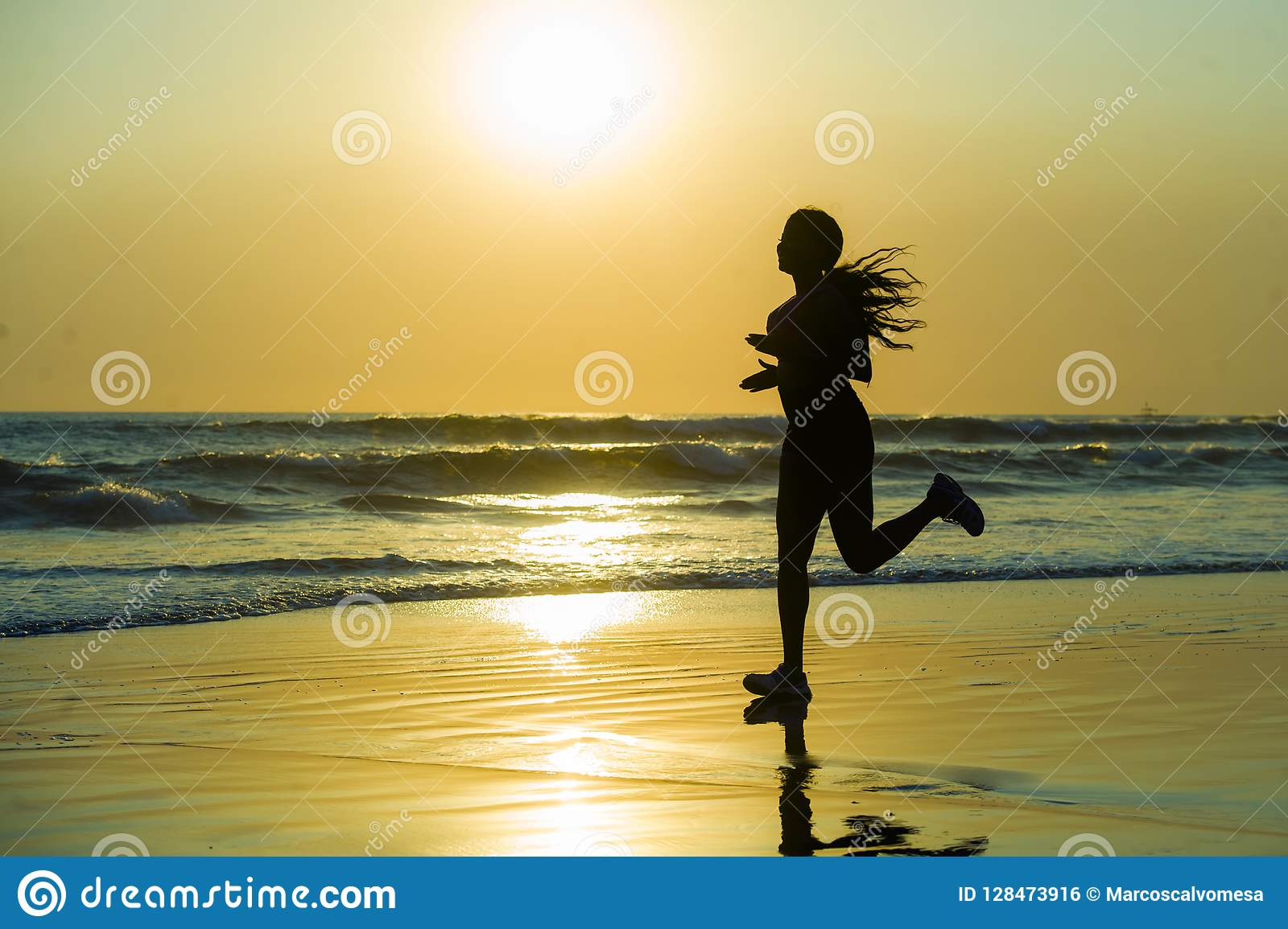 Silhouette of young happy and attractive African American runner woman exercising in running fitness workout at beautiful beach jo