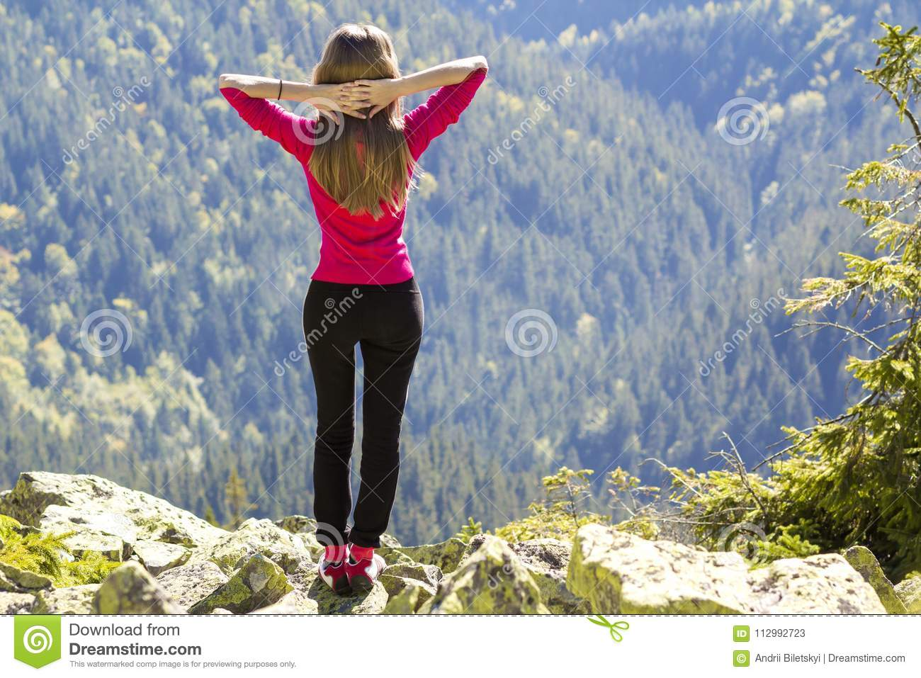 Silhouette of a young happy beautiful slim girl in red sweater standing on big rocks in mountains lifting hands. Tourism and trave