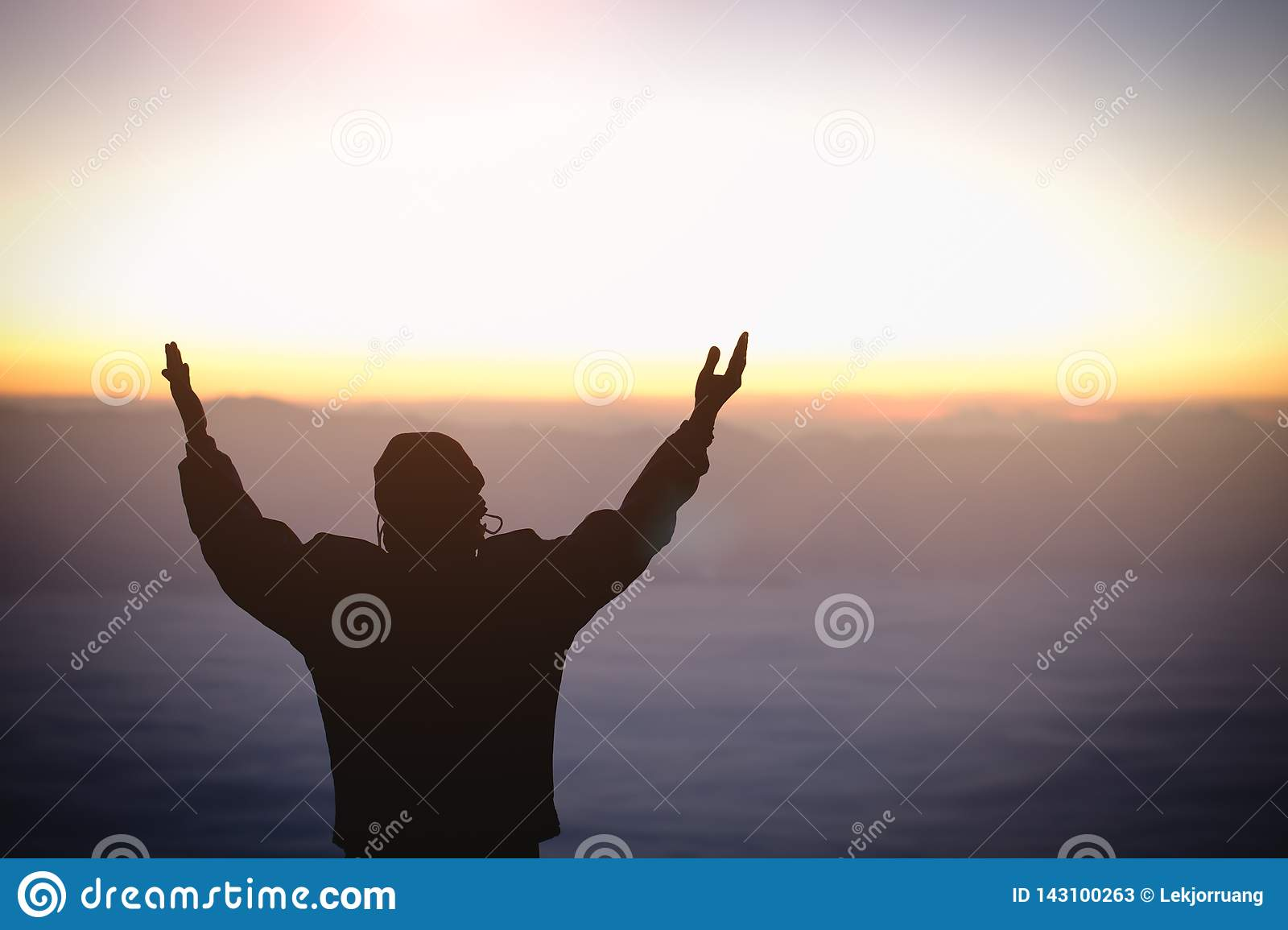 Silhouette of young  human hands open palm up worship and praying to god  at sunrise, Christian Religion concept background
