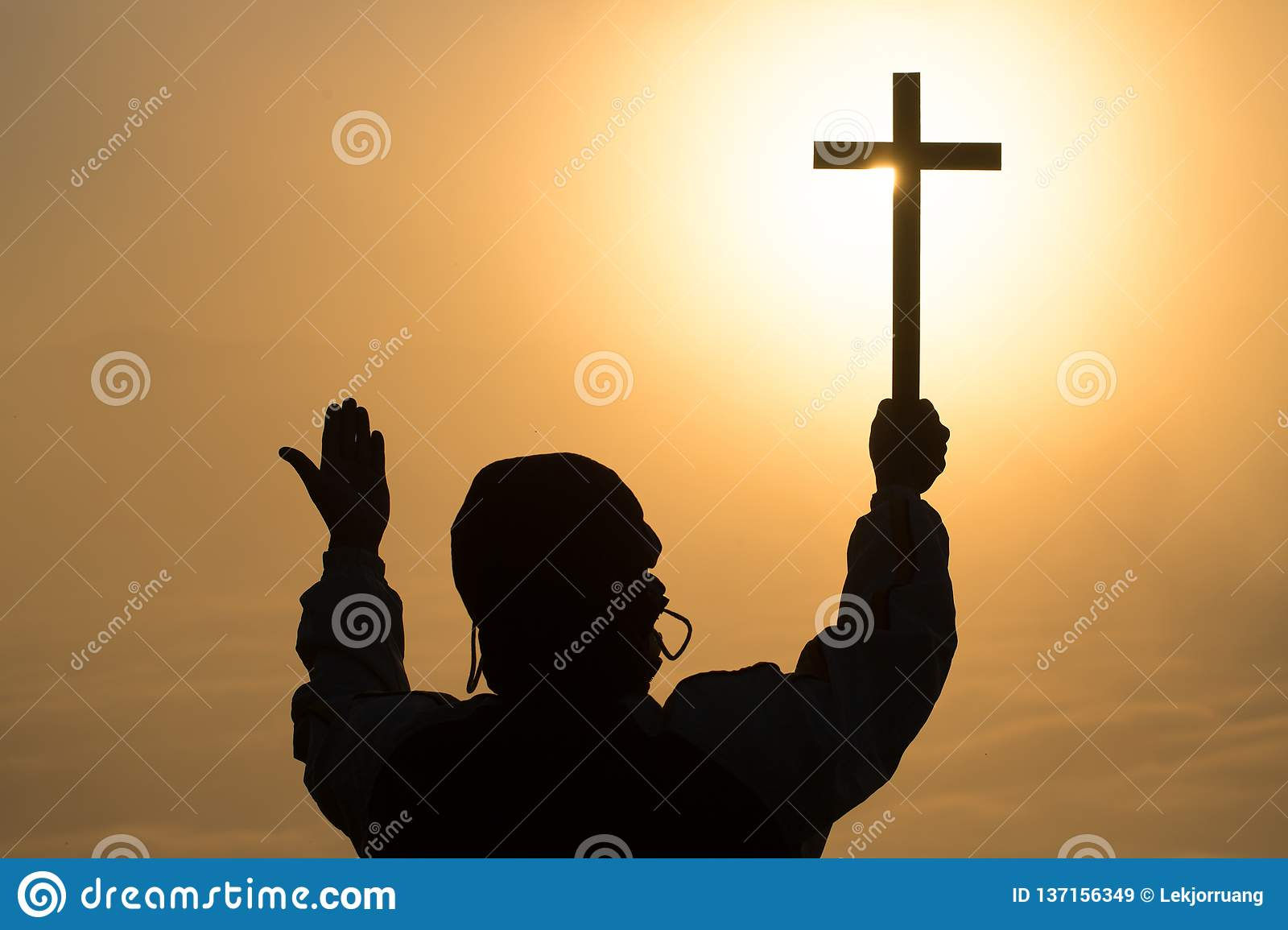 Silhouette of young human hands praying with a cross at sunrise, Christian Religion concept background