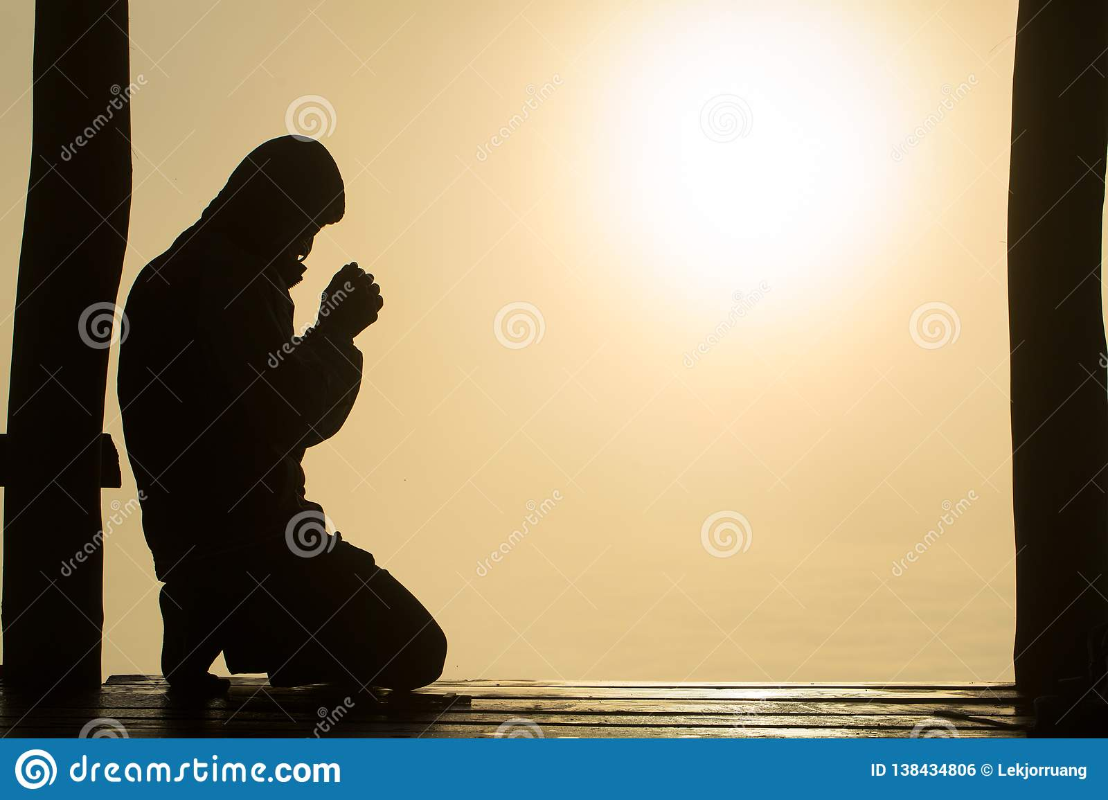 Silhouette of young human hands praying to god at sunrise, Christian Religion concept background