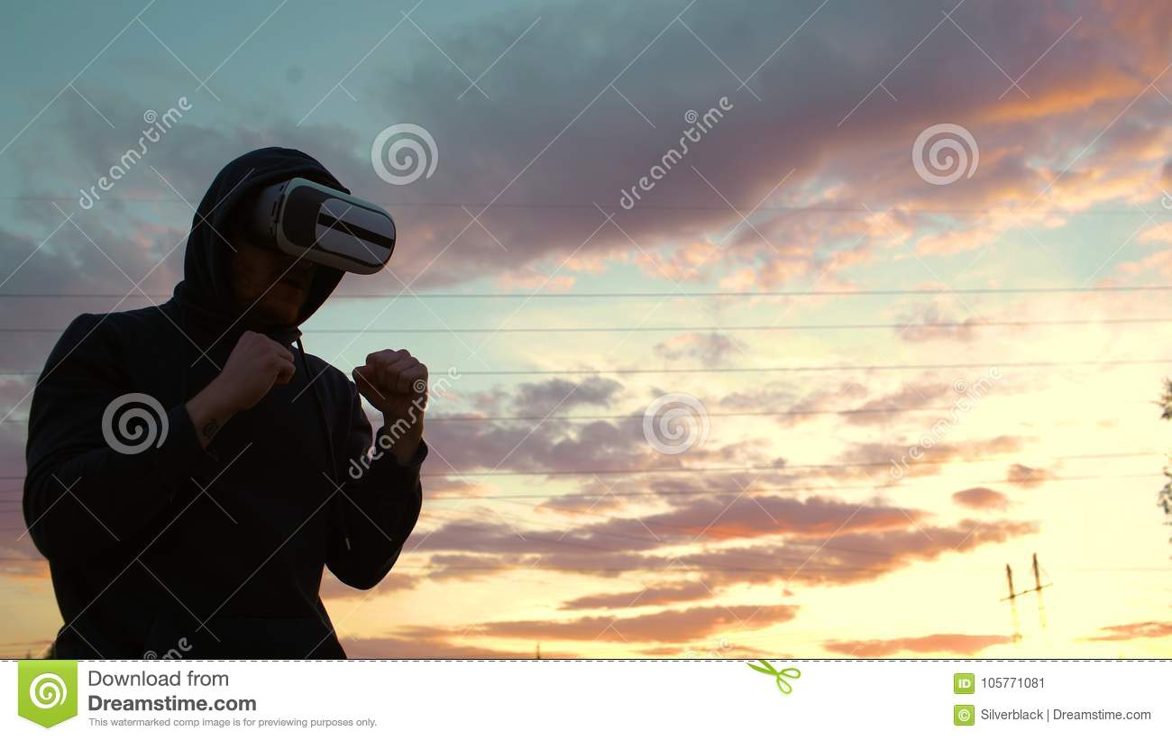 Silhouette of young man boxer in VR 360 headset training for kicking in virtual reality combat on sunset at city park