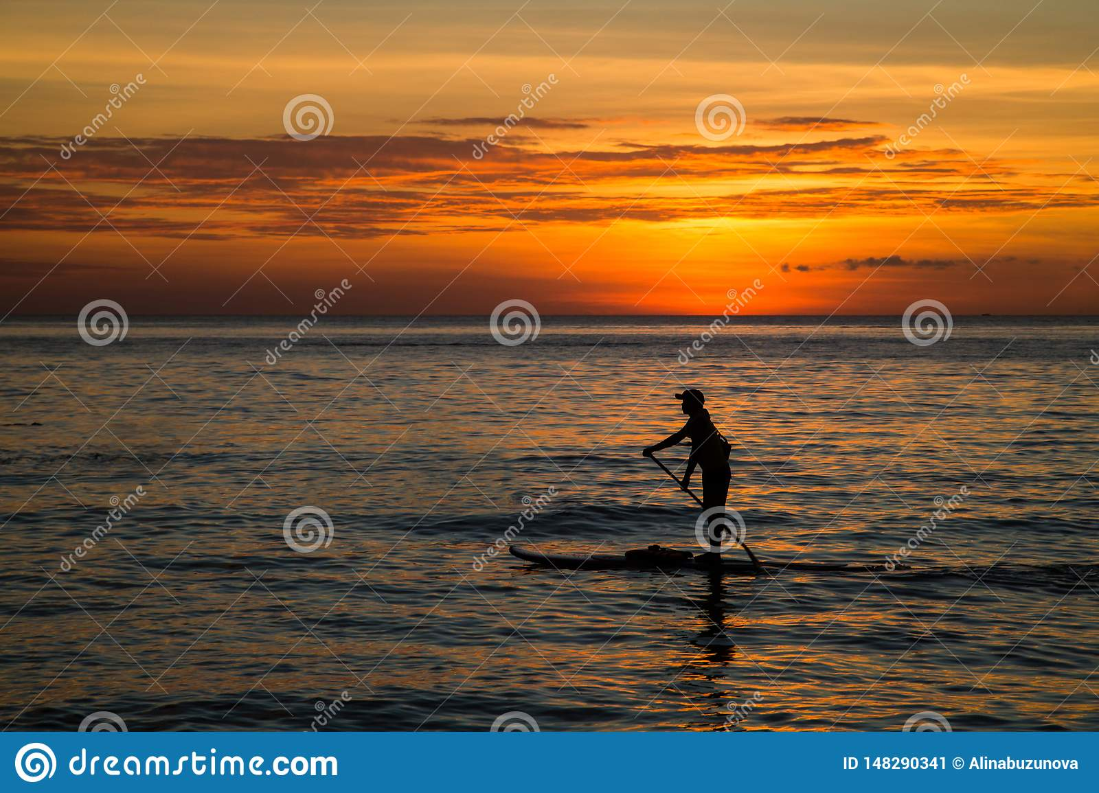 Silhouette of young man paddling on a SUP board in the sea at sunset, rear view