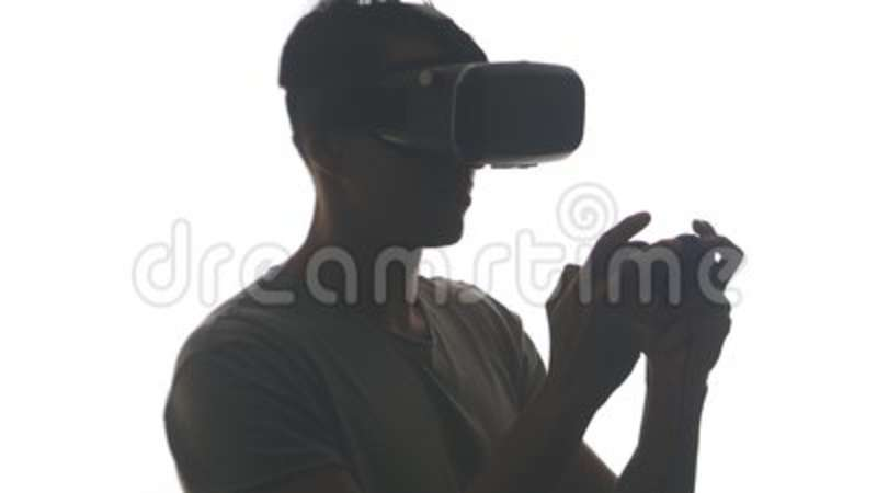 737d7ab077be Silhouette of young man playing game in vr glasses. Guy gets experience  using the virtual reality helmet isolated on.