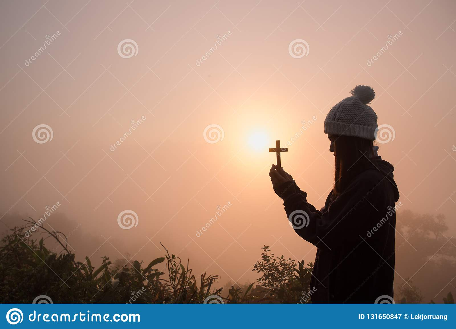 Silhouette of young woman praying with a cross at sunrise, Christian Religion concept background