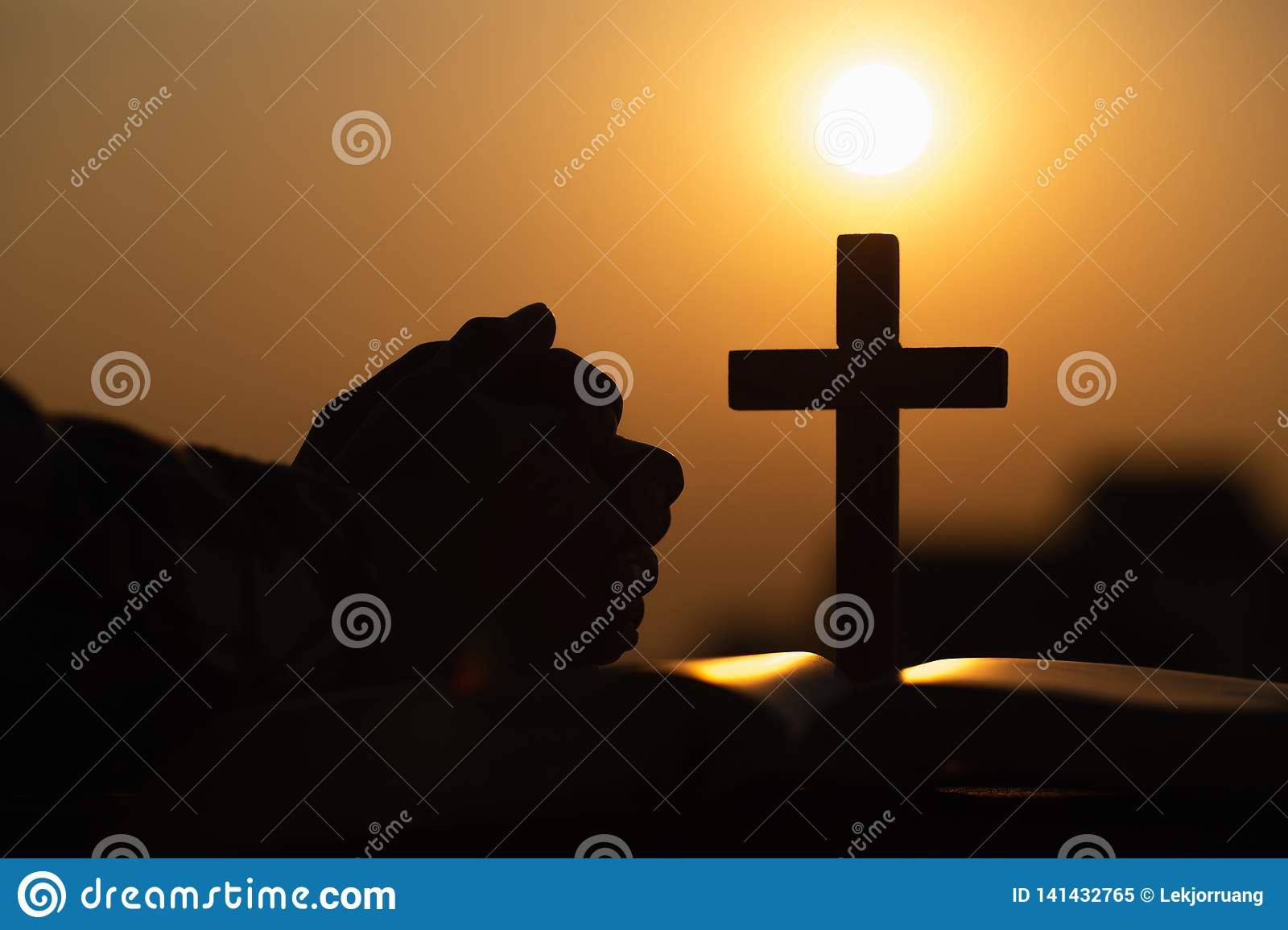 Silhouette of young woman praying with crosses and bibles at sunrise, Christian Religion concept background