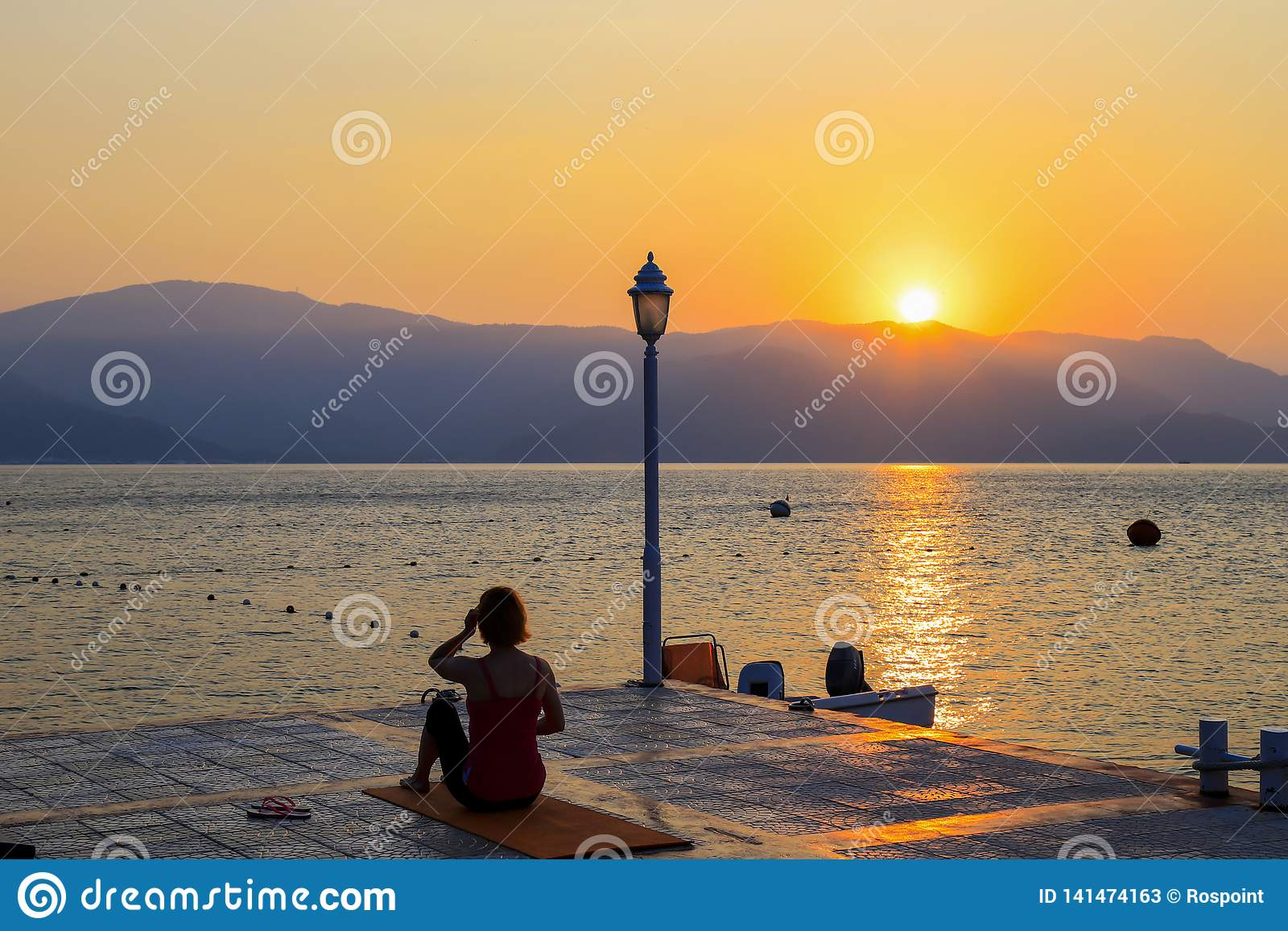 Silhouette of a young woman who performs yoga exercises on a summer morning on the seashore at sunrise. Sports, lifestyle.