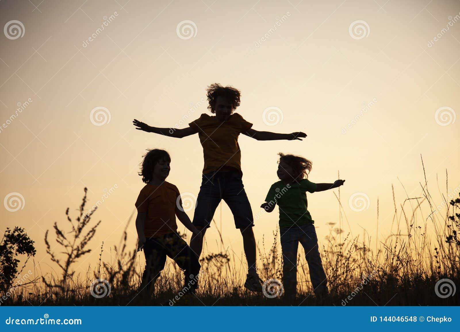 Дети играя скакать на луг захода солнца лета silhouetted