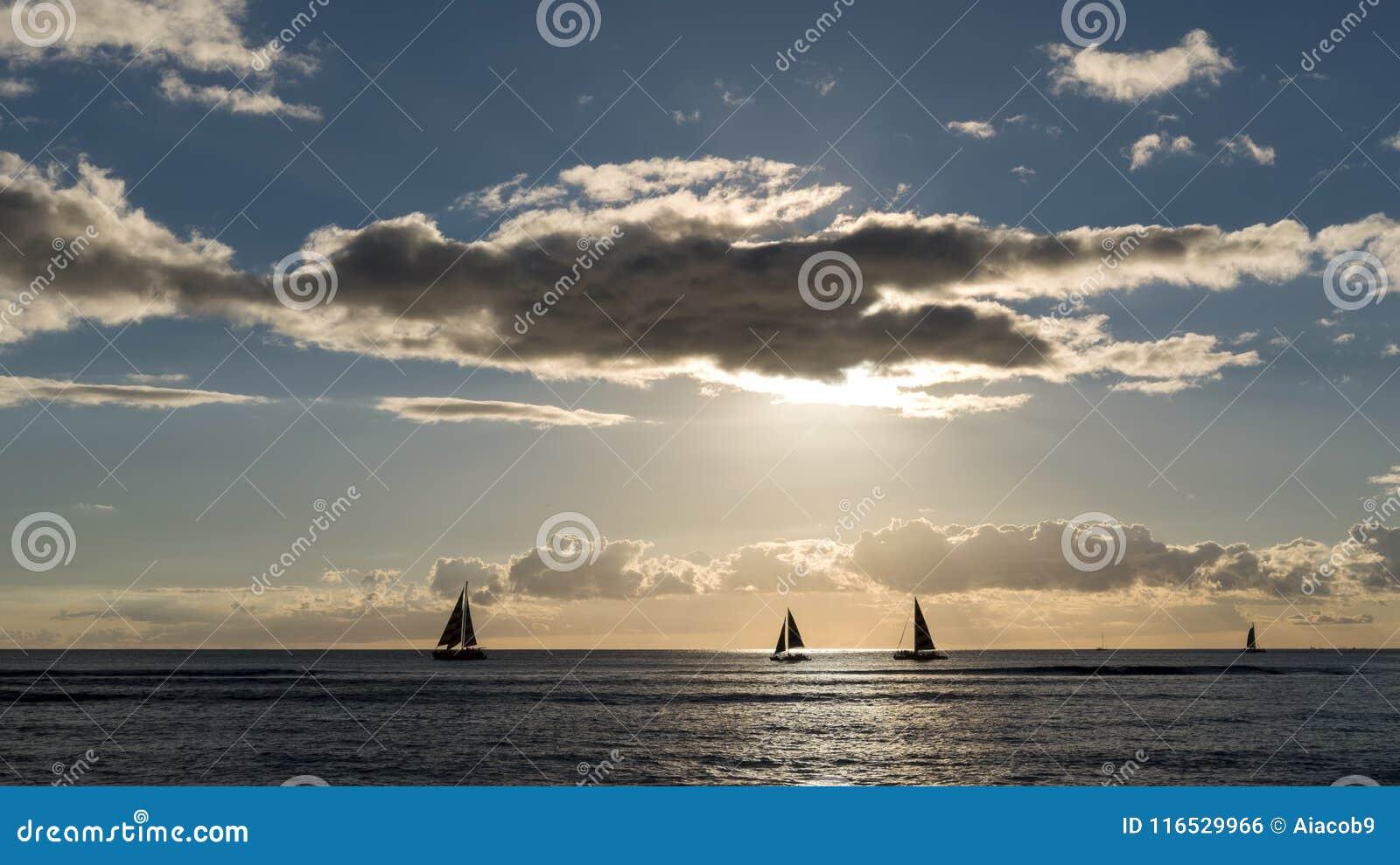 Silhouetted floating sailing boats at the sunset at Waikiki beach, Honolulu, Oahu island, Hawaii, USA