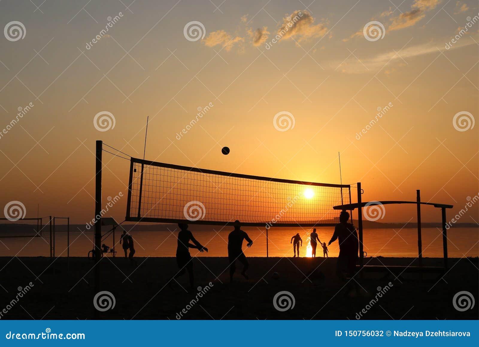 Silhouetten op het strand terwijl het spelen van volleyball bij zonsondergang