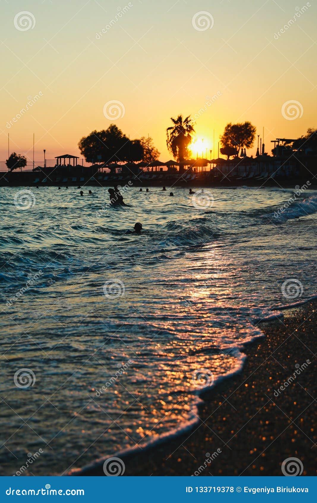 Silhouetten van gelukkige mensen die en in het overzees bij zonsondergang, concept over het hebben van pret op het strand zwemmen