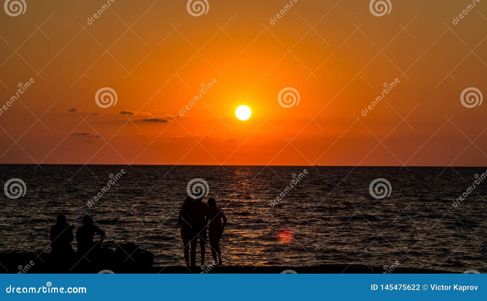 Silhouetten van jongeren bij zonsondergang en overzeese voorzijde