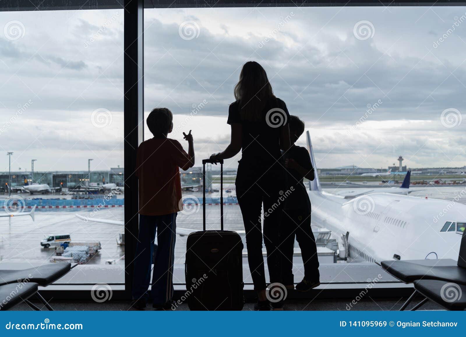 Silhouetten van mamma met jonge geitjes in terminal die op vlucht wachten