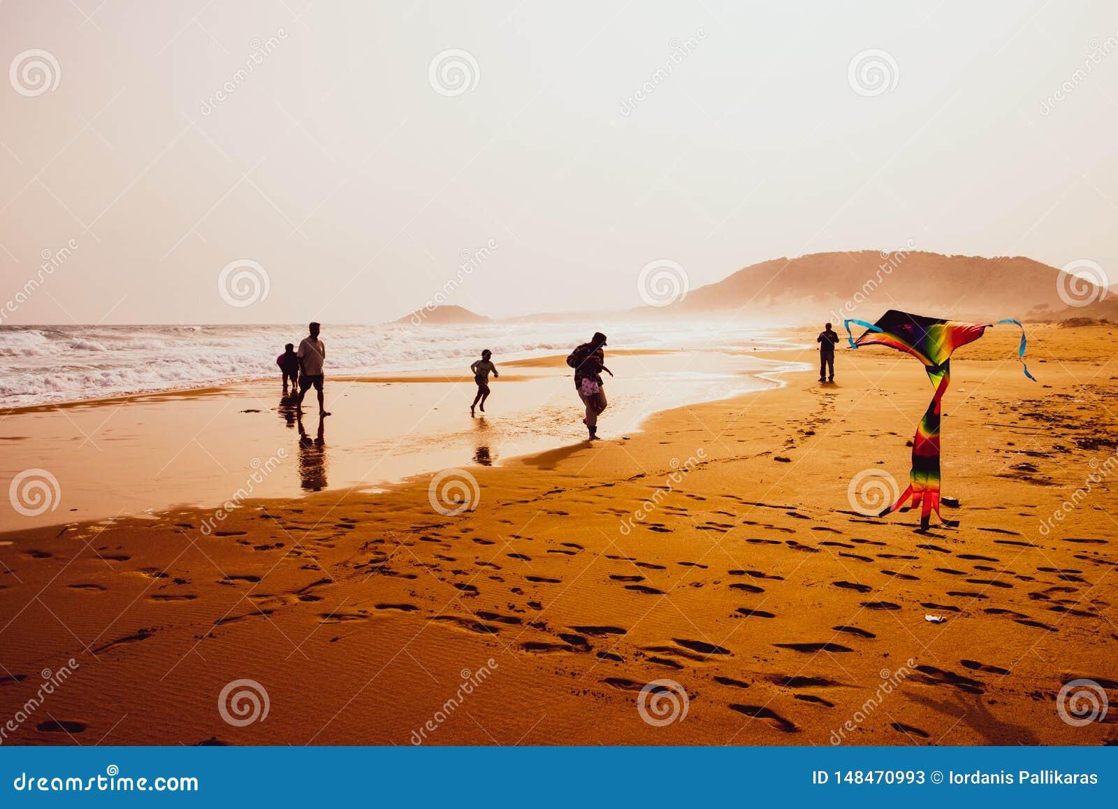 Silhouetten van mensen die en een vlieger in zandig Gouden Strand, Karpasia, Cyprus spelen vliegen